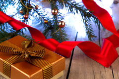 Gift box with golden ribbon and Christmas decoration over wooden table Royalty Free Stock Photos