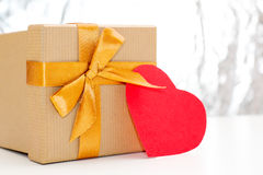 Gift box with Golden ribbon and red heart lies on a white table on silver glittering background. Stock Photo
