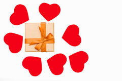 Gift box with Golden ribbon and some red hearts around on white background. Festive concept for Valentine`s day, birthday, wedding, party, holiday Stock Photo
