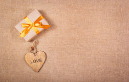 Gift box with a golden ribbon and a wooden heart. Romantic concept. Copy space Royalty Free Stock Photography