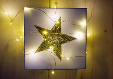 CHRISTMAS GIFT - GIFT BOX WITH GOLDEN STAR AND LIGHT CHAIN. Gift box with golden star and CHRISTMAS LIGHT CHAIN Royalty Free Stock Image