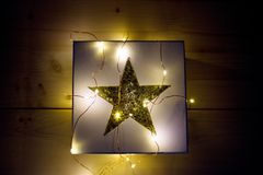 CHRISTMAS GIFT - GIFT BOX WITH GOLDEN STAR AND LIGHT CHAIN. Gift box with golden star and CHRISTMAS LIGHT CHAIN Royalty Free Stock Photo
