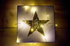 CHRISTMAS GIFT - GIFT BOX WITH GOLDEN STAR AND LIGHT CHAIN. Gift box with golden star and CHRISTMAS LIGHT CHAIN Stock Images