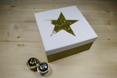 CHRISTMAS GIFT - GIFT BOX WITH GOLDEN STAR. Gift box with golden star and two jingle bells Royalty Free Stock Images