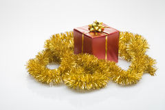 Gift box and golden tinsel Stock Photography