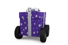 Gift box with gray ribbon on wheels Stock Photos