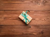 Gift box with green ribbon on the center wood antique rustic bro. Wn table. A surprise gift in brown Kraft paper Stock Photos
