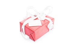Gift box with a greetings card. Close-up shot of a red gift box with white ribbons and a greetings card attached to it  on white background Stock Images