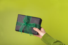 Gift box in a hand. Female hand holds black gift box tied with green ribbon, green background Royalty Free Stock Photography