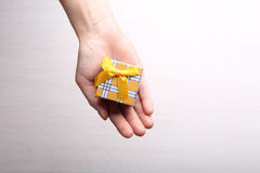 Gift box in hand on light wooden background Royalty Free Stock Photos