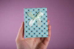 Gift box in hand on lilac background Royalty Free Stock Photography