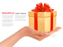 Gift box in hand with red bow and ribbons. Royalty Free Stock Images