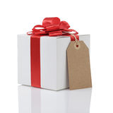 Gift box with handmade red ribbon bow and tag Royalty Free Stock Photos