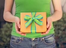 Gift box in hands. Girl holding a gift box with decorative ribbon Stock Images
