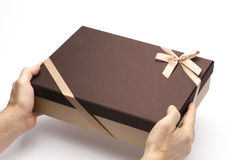 The gift box in hands to hold on a white background. Cardboard box for gift packing Stock Photo