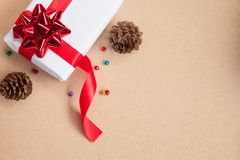 Gift box have bind from red ribbon with decoration items of Christmas day. And holiday day concept etc, on brown background Royalty Free Stock Photos