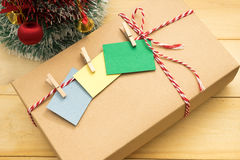 Gift box have post it note with wooden clip on top putting. Brown gift box have post it note with wooden clip on top putting on wooden background Royalty Free Stock Photography