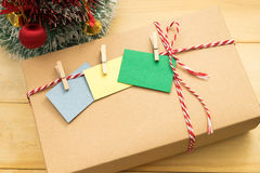 Gift box have post it note with wooden clip on top putting on wo. Brown gift box have post it note with wooden clip on top putting on wooden background Stock Images