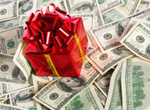 Gift box on heap of money. Red gift box on heap of $100 dollar bills Stock Photos