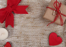 Gift box, heart and bow on sackcloth texture Stock Image