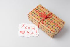 Gift box with heart design prints  and  I love paper card on light gray background. Saint Valentine`s Day concept Royalty Free Stock Photos