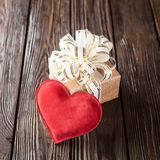 Gift box and heart. On old wooden background Stock Image