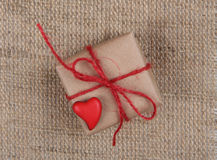 Gift box and heart on sackcloth texture Royalty Free Stock Photography