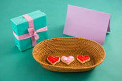 Gift box, heart shape cookies and blank card against green background Royalty Free Stock Photography