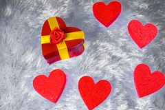 Gift box in heart shape surrounded by decorative hearts on the cover simulating the fur. Copy paste Royalty Free Stock Images