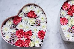 Gift box with heart shaped flowers on grey marble background royalty free stock images