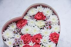 Gift box with heart shaped flowers on grey marble background stock photos