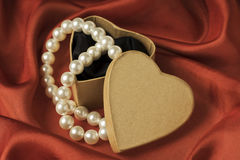 Gift box. Heart shaped gift box with pearls. Red Valentines day, birthday or celebration background Royalty Free Stock Photography