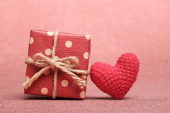 Gift box and heart shaped on red background. Stock Photography