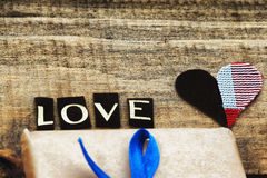 Gift box and heart shapes on a table Royalty Free Stock Image