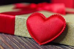 Gift box and heart on wooden background.  Royalty Free Stock Photos