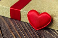 Gift box and heart on wooden background.  Stock Photos