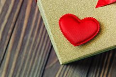 Gift box and heart on wooden background.  Stock Photo