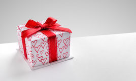 Gift box with hearts printed with diagonal grey background Royalty Free Stock Photo