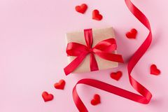 Gift box, hearts and red ribbon on pink pastel background for Valentines day card. Flat lay style stock image