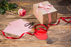 The gift box with hearts on wooden background Royalty Free Stock Photography