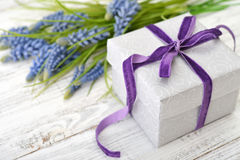 Gift box with hyacinth. Gift box with violet ribbon and bouquet of hyacinth on wooden background Royalty Free Stock Photo