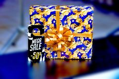 Gift box with the inscription 50% sale, gold on a blue background royalty free stock images