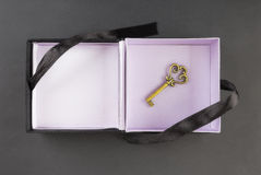 Gift box with a key at the bottom on a black Stock Image