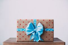 Gift box in kraft paper in polka dots with a blue ribbon. Gift box in kraft paper in polka dots with a blue ribbon on a wooden table royalty free stock photos