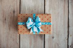 Gift box in kraft paper in polka dots with a blue ribbon on a wooden background. Top View stock photography