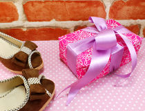 Gift box and ladies shoes on pink polka dot background Stock Photo
