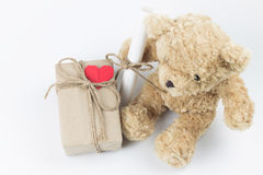 Gift box and letter roll put beside a teddy bear. Gift box and letter roll put beside a teddy bear on white background. Top view Stock Image