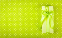 Gift box on light green background. Box with surprise on  polka dot background. International Women`s Day. Copy space. Top view. Gift box on light green Stock Photography