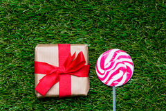 Gift box and lollipop candy on green grass background, above poi Stock Images
