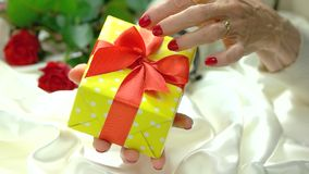 Gift box and luxury manicure, slow motion. Old woman hand with beautiful red manicure holding gift box with red bow close up. Birthday gift and anniversary stock video footage